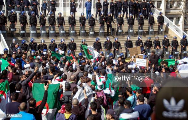 TOPSHOT Algerians shout slogans and raise signs and national flags as they protest outside the city hall in the northern coastal city of Oran about...