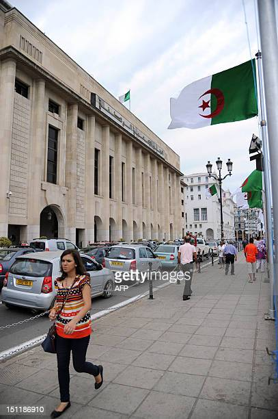 Algerians walk past the National Assembly building in the capital Algiers on September 3 as the parliament held its new session following legislative...