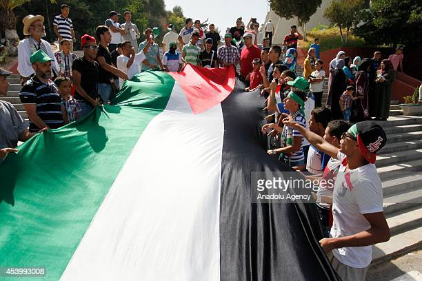 Algerians wave Palestinian flag as they protest against ongoing Israeli attacks on Gaza in Algiers Algeria on August 22 2014
