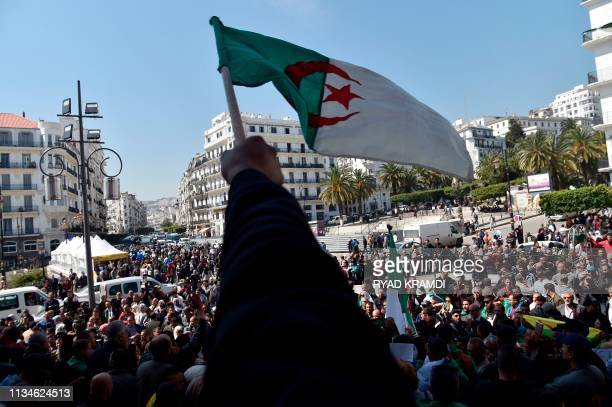 Algerians wave the national flag as they demonstrate to demand sweeping change to the country's whole political system in Algiers on April 3...