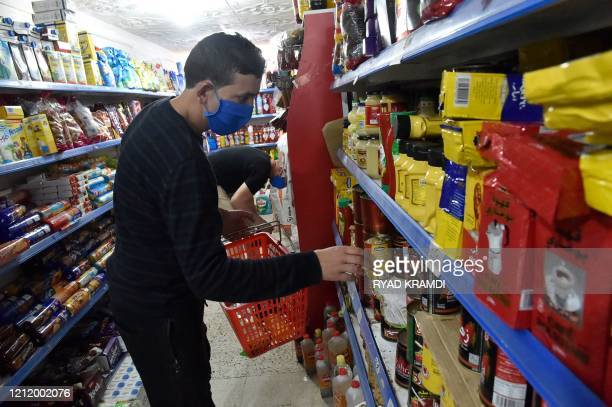 Algerians wearing protective masks buy goods at a supermarket in the capital Algiers during the Muslim holy month of Ramadan on May 6 2020 This year...