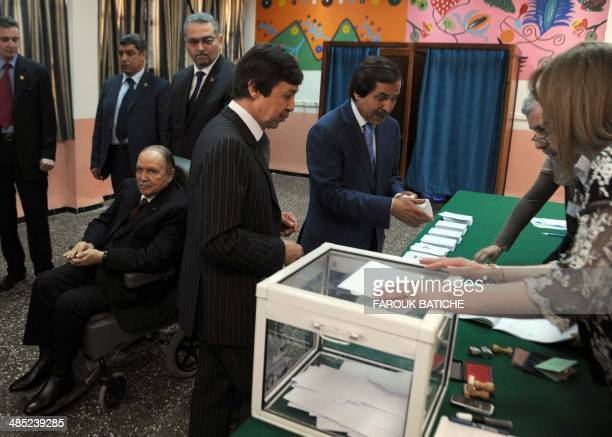 Algeria's ailing President Abdelaziz Bouteflika running for reelection watches after casting his ballot from a wheelchair as his brothers Said who...
