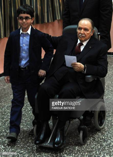 Algeria's ailing President Abdelaziz Bouteflika running for reelection is pushed in a wheelchair next to his nephew before casting his ballot at a...