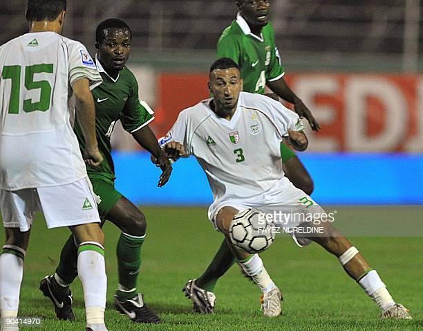 Algeria's Belhadj Nadir fights for the with Zambia's Musonda Joseph as Algerian Karim Ziani looks on during their 2010 World Cup African zone group C...