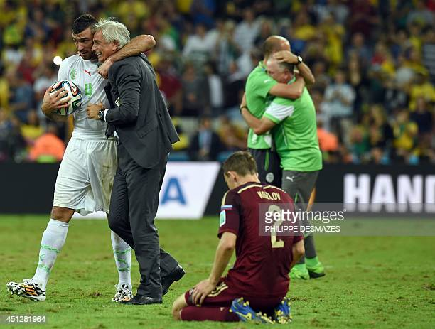 Algeria's Bosnian coach Vahid Halilhodzic celebrates with Algeria's defender Essaid Belkalem as Russia's defender Alexei Kozlov kneels on the ground...