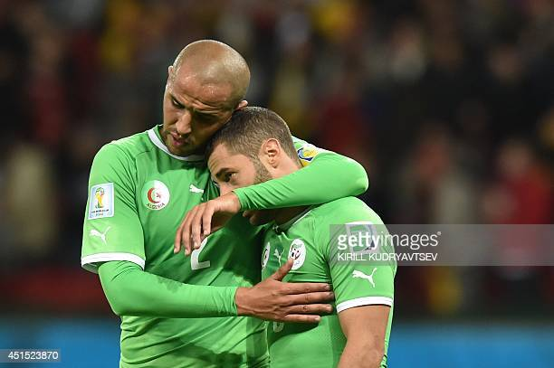Algeria's defender and captain Madjid Bougherra and Algeria's midfielder Medhi Lacen react after losing their Round of 16 football match against...