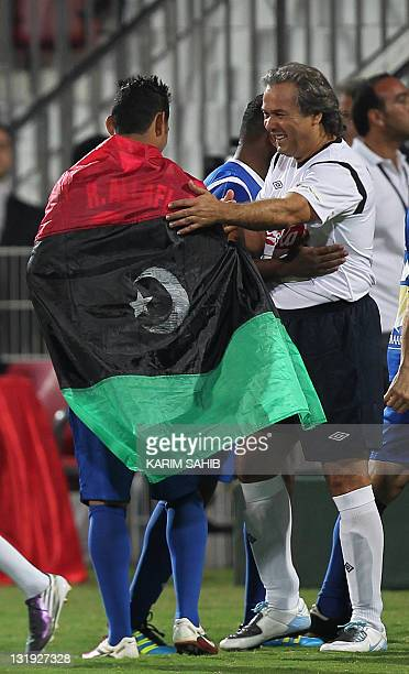 Algeria's former football player Mustapha Rabah Madjer greets an unidentified player wrapped with Libya's new flag during an allstar international...