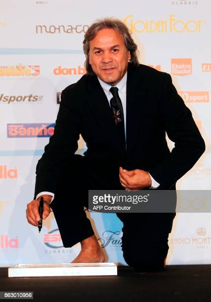 Algeria's former football player Mustapha Rabah Madjer signs his footprint on a slab of moulding compound on October 10 2011 in Monaco during the...