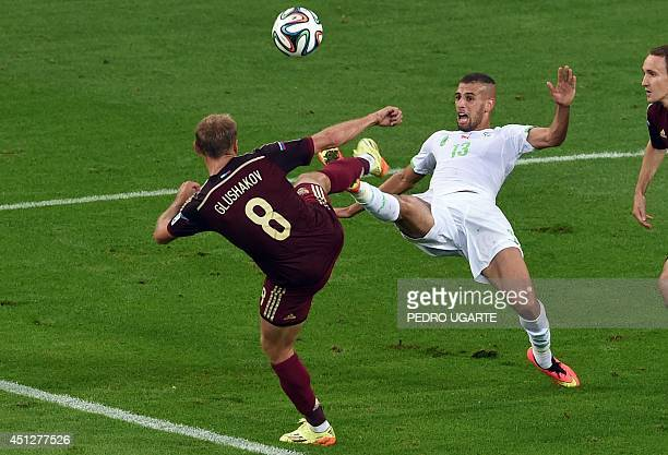Algeria's forward Islam Slimani and Russia's midfielder Denis Glushakov compete for the ball during the Group H football match between Algeria and...