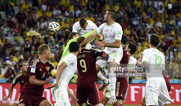 Algeria's forward Islam Slimani heads the ball to score a goal during the Group H football match between Algeria and Russia at The Baixada Arena in...
