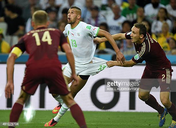 Algeria's forward Islam Slimani reacts as Russia's defender Aleksei Kozlov pulls at his shorts during a Group H football match between Algeria and...