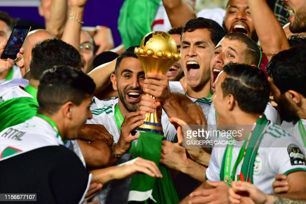 TOPSHOT Algeria's forward Riyad Mahrez and his teammates celebrate with the trophy after winning the 2019 Africa Cup of Nations Final football match...