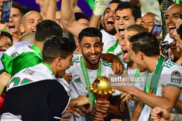 Algeria's forward Riyad Mahrez and his teammates celebrate with the trophy after winning the 2019 Africa Cup of Nations Final football match between...