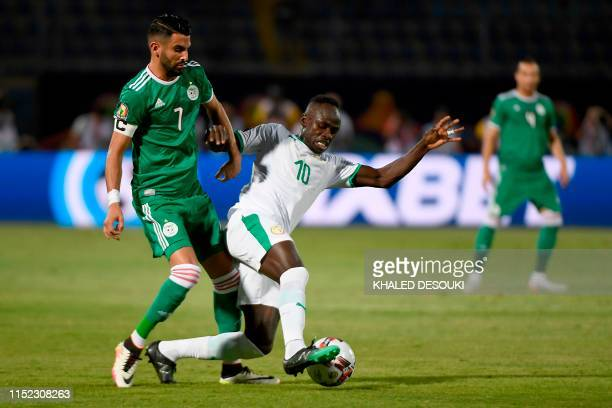Algeria's forward Riyad Mahrez fights for the ball with Senegal's forward Sadio Mane during the 2019 Africa Cup of Nations football match between...