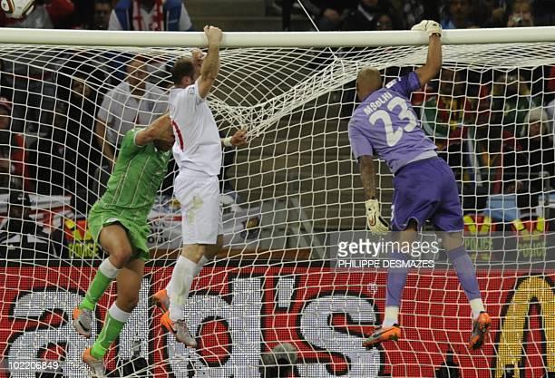 Algeria's goalkeeper M'bolhi Rais Ouheb defender Madjid Bougherra and England's striker Wayne Rooney jump on the goal's crossbar after England missed...