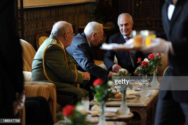 Algeria's Interior Minister Tayeb Belaiz speaks with Minister of War veterans Mohamed Cherif Abbas and chief of staff General Ahmed Gaid Salah at the...