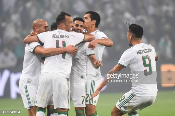 Algeria's midfielder Riyad Mahrez celebrates with his teammates after scoring a goal during the international friendly football match between Algeria...