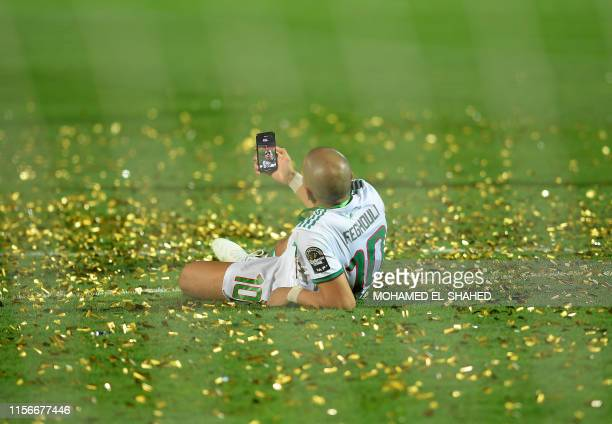 TOPSHOT Algeria's midfielder Sofiane Feghouli celebrates after winning the 2019 Africa Cup of Nations Final football match between Senegal and...