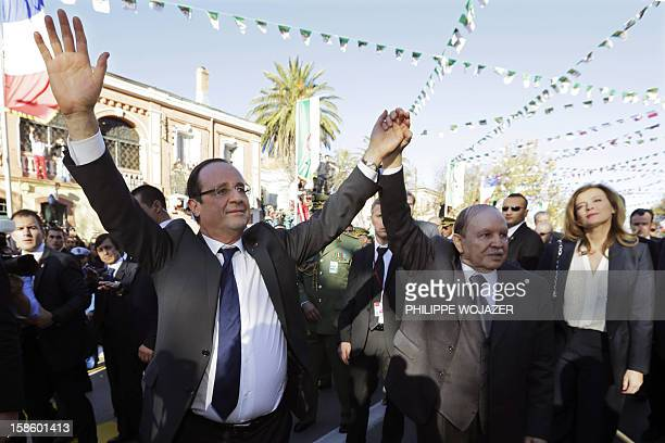 Algeria's President Abdelaziz Bouteflika and his French counterpart Francois Hollande raise their arms as they walk in Tlemcen on December 20 2012...