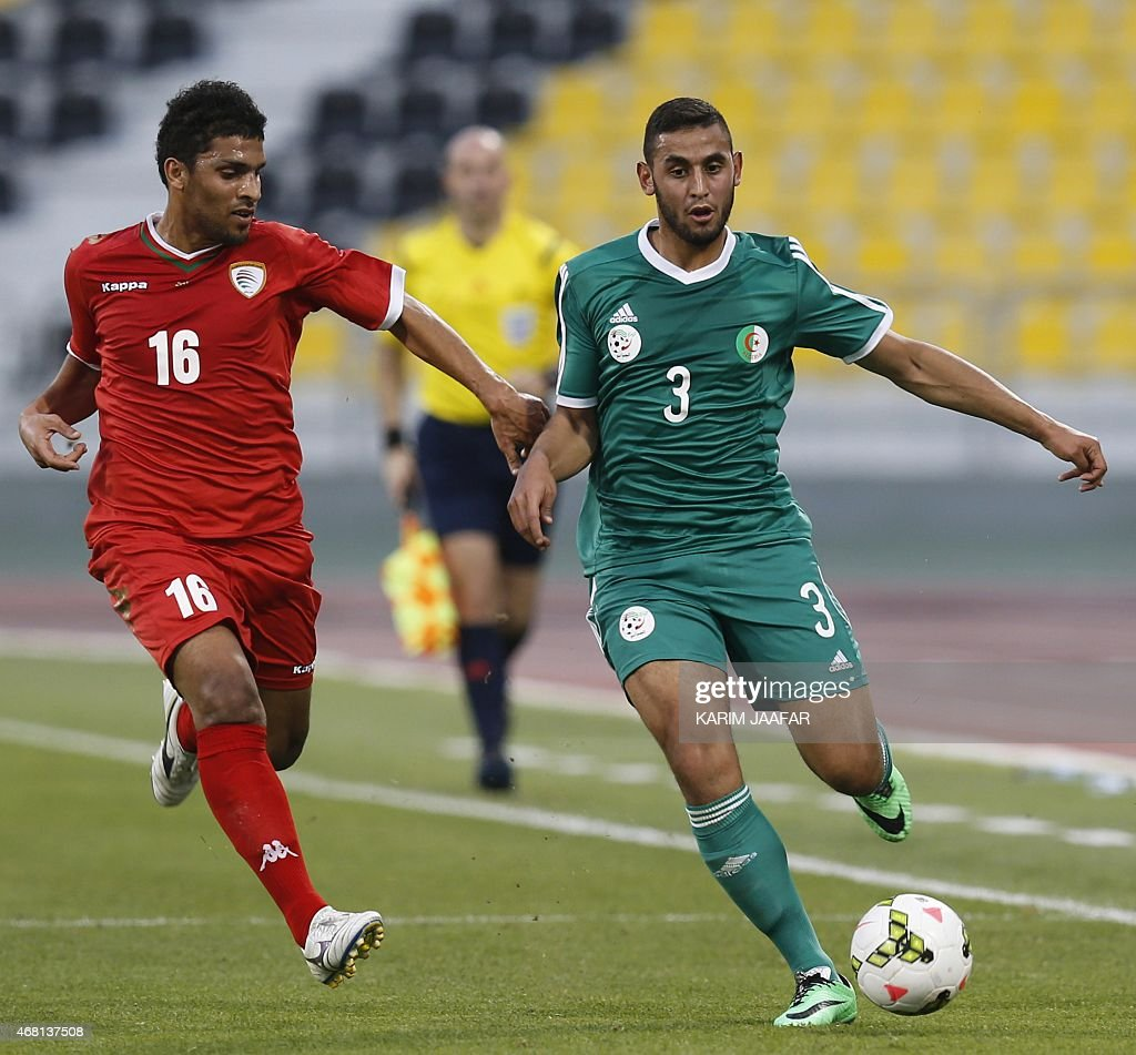 Algeria's Raed Ibrahim (R) is challenged by Oman's Yaqoob Al-Qasmi as he dribbles the ball during their friendly football match on March 30, 2015 at the Qatar Club Stadium in Doha, as part of the preparations for the second round of the 2018 World Cup's Asian leg qualifiers.