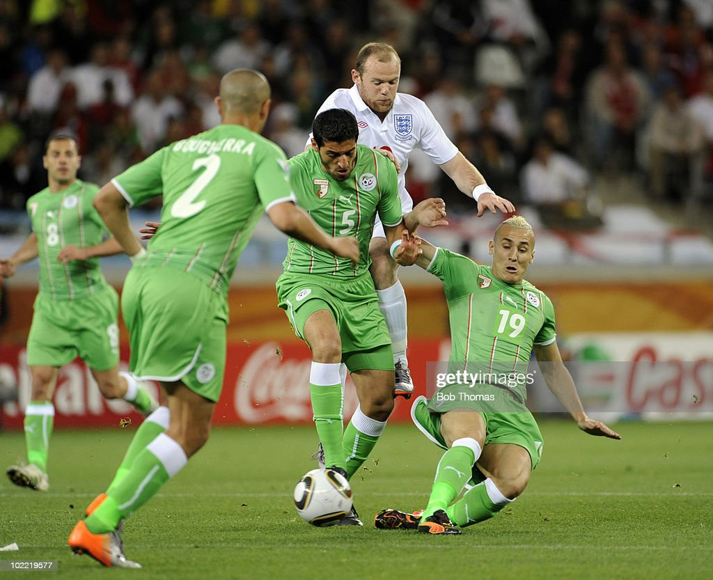 Algeria's Rafik Halliche (5) and Hassan Yebda (19) keep out Wayne Rooney of England during the 2010 FIFA World Cup South Africa Group C match between England and Algeria at Green Point Stadium on June 18, 2010 in Cape Town, South Africa. The match was drawn 0-0.