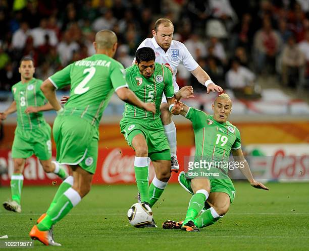 Algeria's Rafik Halliche and Hassan Yebda keep out Wayne Rooney of England during the 2010 FIFA World Cup South Africa Group C match between England...