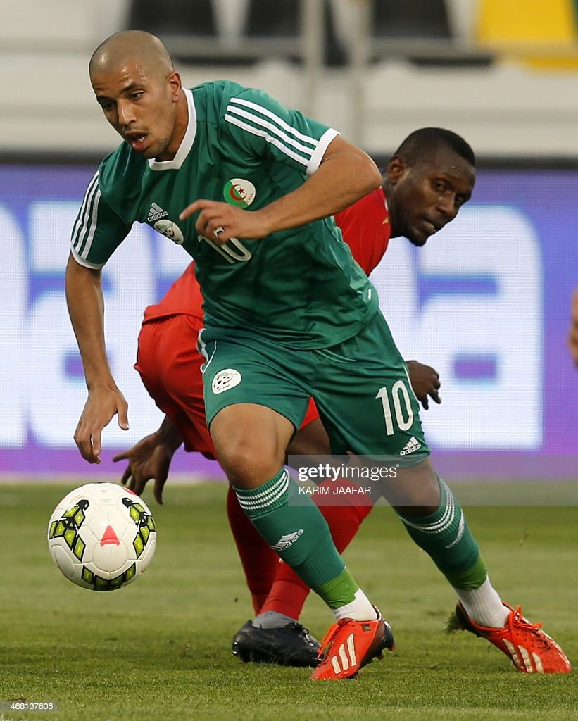 Algeria's Sofiane Feghouli (front) dribbles the ball during their friendly football match against Oman on March 30, 2015 at the Qatar Club Stadium in Doha, as part of the preparations for the second round of the 2018 World Cup's Asian leg qualifiers.