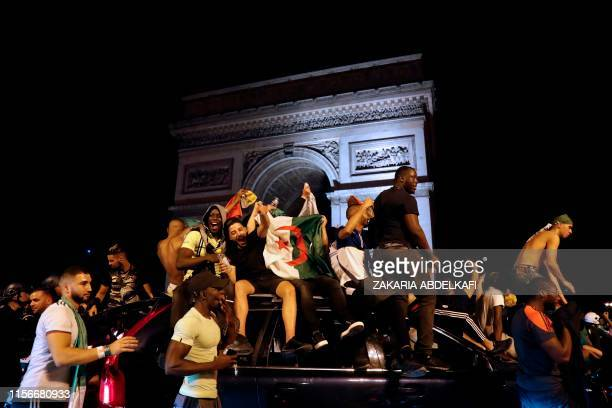 Algeria's supporters celebrate in front of the Arc de Triomphe on the Champs Elysee Avenue in Paris, after Algeria won 1-0 the 2019 Africa Cup of...
