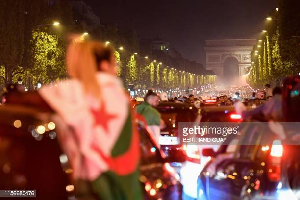 TOPSHOT Algeria's supporters celebrate with the Algerian national flag in front of the Arc de Triomphe on the Champs Elysee Avenue in Paris after...