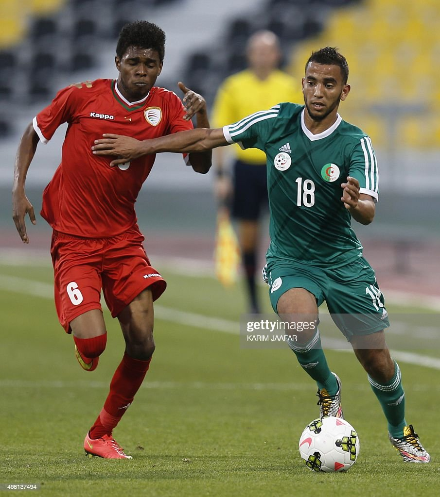 Algeria'sIbrahim Chenihi (R) vies for the ball against Oman's Raed Ibrahim during their friendly football match on March 30, 2015 at the Qatar Club Stadium in Doha, as part of the preparations for the second round of the 2018 World Cup's Asian leg qualifiers.