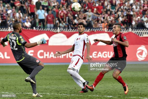 USM Alger's Oussama Darfalou vies for the ball with Wydad's Ahmed Reda Tagnaouti and Amine Atouchi during the CAF Champions League semifinal football...