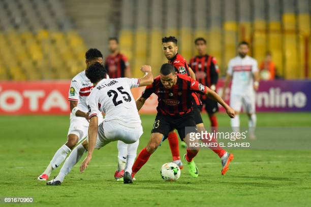 USM Alger's player Darfalou vies for the ball with Egypt Zamalek's player Ali Gabr during the African Champions League group stage football match...