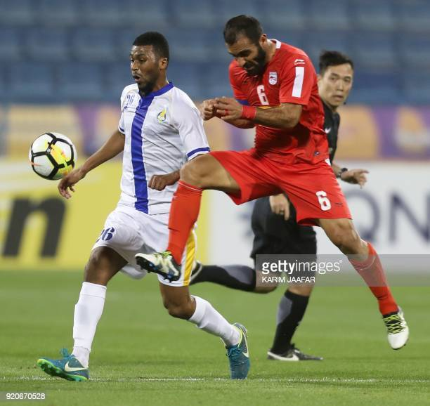 AlGharafa's Abdulaziz Hatem and Tractor Sazi's Mehdi Kiani vie for the ball during the AFC Champions League Group A football match between Qatar's...