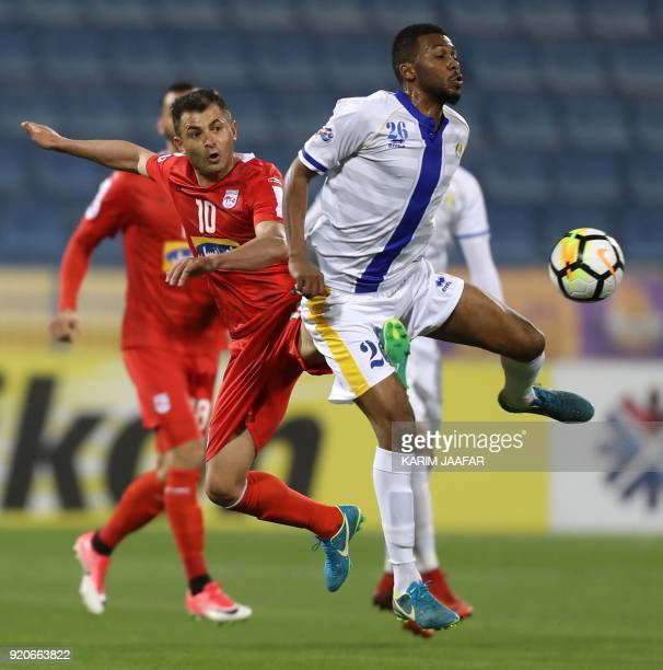 AlGharafa's Abulaziz Hatem is kicked in the crotch by Tractor Sazi's Mohammad Ebrahimi during the AFC Champions League Group A football match between...