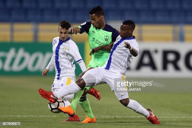 AlGharafa's defender Monkez and midfielder Assim Madibo vie for the ball with alAhli's forward Salman Moasher during the AFC Champions League...