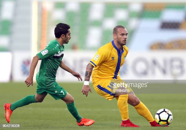 AlGharafa's Dutch midfielder Wesley Sneijder passes the ball as he is marked by AlAhli's Mohsen alYazidi during their Qatar Stars League football...