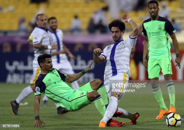 AlGharafa's forward Ahmed Alaaeldin is tacked by alAhli's midfielder Waleed Bakshween during the AFC Champions League football match between...