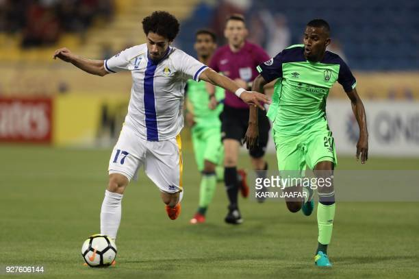 AlGharafa's forward Ahmed Alaaeldin vies for the ball with alAhli's defender Ageel AlSahbi during the AFC Champions League football match between...