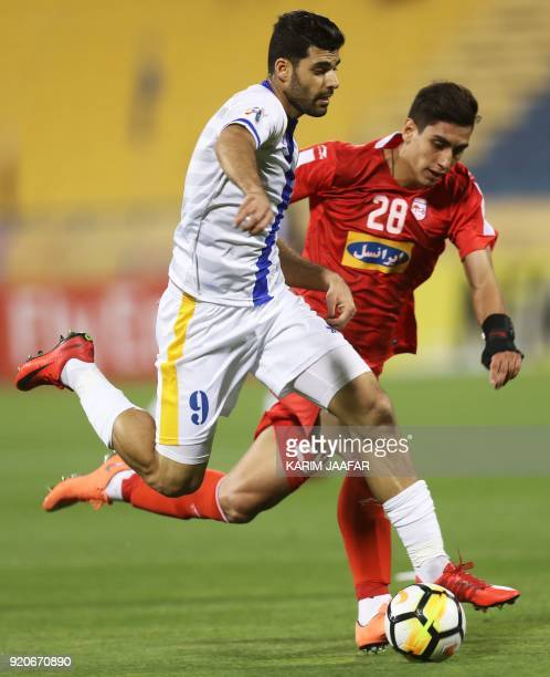 AlGharafa's Mehdi Taremi and Tractor Sazi's Mohammad Naderi vie for the ball during the AFC Champions League Group A football match between Qatar's...