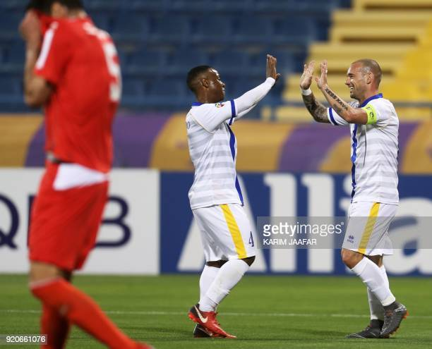 AlGharafa's Wesley Sneijder and Assim Madibo celebrate after their team scored a goal during the AFC Champions League Group A football match between...