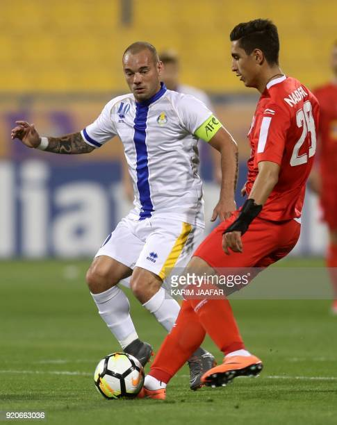 AlGharafa's Wesley Sneijder and Tractor Sazi's Mohammad Naderi vie for the ball during the AFC Champions League Group A football match between...