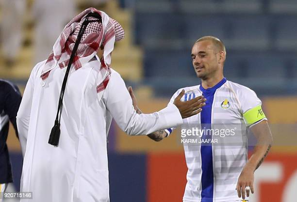 AlGharafa's Wesley Sneijder shakes hands with the team manager Saad AlShammari after winning the AFC Champions League Group A football match between...