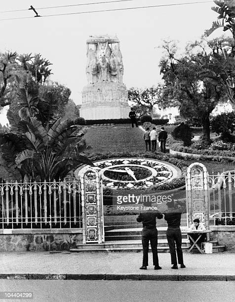 Algiers a view of the monument consacrated to the dead and of the floral clock on Laferriere Square before which two French recruits take photographs...