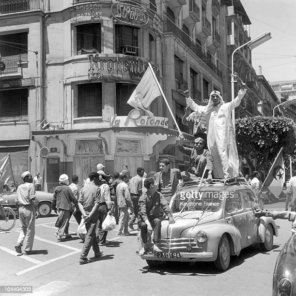 Algiers after the publication of the referendum results in favor of Algeria's self-determination inhabitants of the city, perched on a car, acclaim...