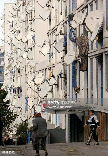 Picture taken 28 December 2005 shows Algerians walking next apartment buildings full of satellite dishes set up on balconies in the overcrowded...