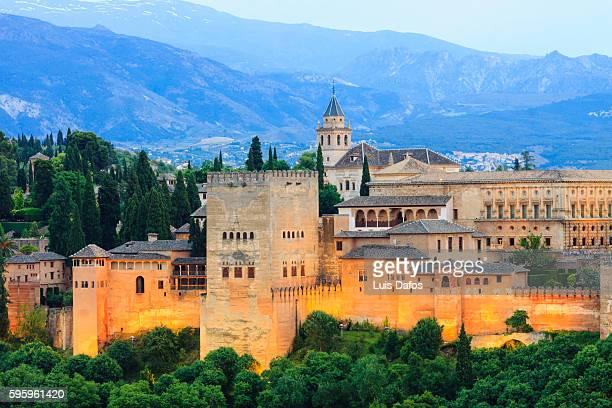 alhambra illuminated at dusk - alhambra granada fotografías e imágenes de stock