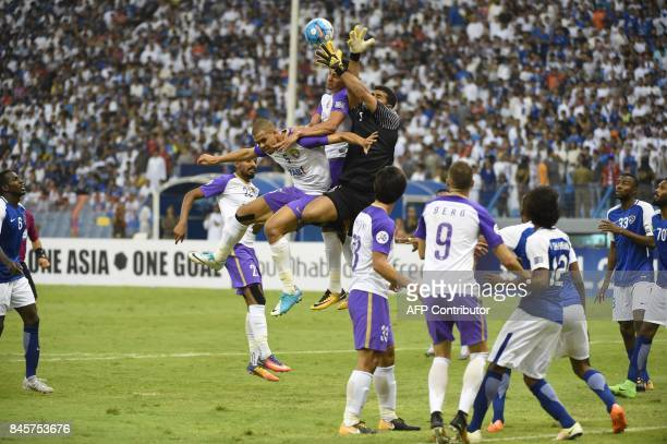 Al-Hilal's goalkeeper Abdullah Muaiouf vies for the ball with Al-Ain's players during their AFC Asian Champions League Group C football match at the...