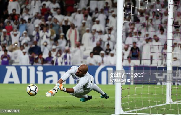 AlHilal's goalkeeper Ali AlHabsi saves a penalty during the AFC Champions League football match between UAE's alAin and Saudi's alHilal at the Hazza...