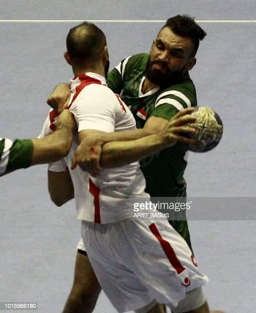 Ali Adnan Chyad Abdlkan of Iraq tries to block Husain Mohamed of Bahrain during the 18th Asian Games Group D men's handball match in Cibubur on...