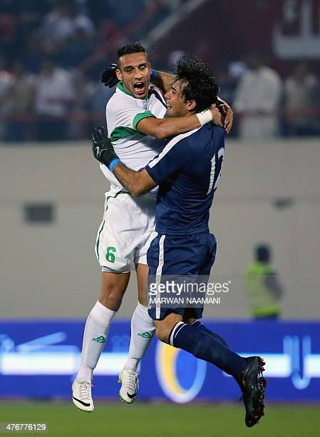 Ali Adnan Kadhim alTameemi of Iraq celebrates with goalkeeper Jalal Hassan Hachim after winning against China their qualification football match for...